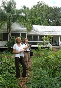 Angela Withers, president of the Henry Nehrling Society, and Theresa Schretzmann-Myers, vice president, in the garden behind the Nehrling house.