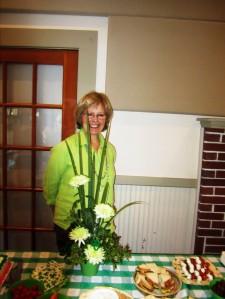 Hostess Carol W. and her floral arrangement centerpiece