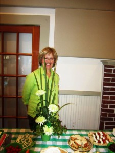 Hostess Carol W. and her floral arrangement centerpiece