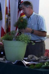 Speaker Tom MacCubbin creates a fall pot of herbs.