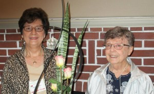 Hostess Paula R. on the left and Hostess Joan P. with the snack table's centerpiece which is a floral arrangement created by Joan P. Not shown is hostess Cannon S.