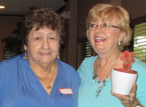 Past President Peggy C. on the left gives President Bonnie B. a blooming cactus for agreeing to another term as president.