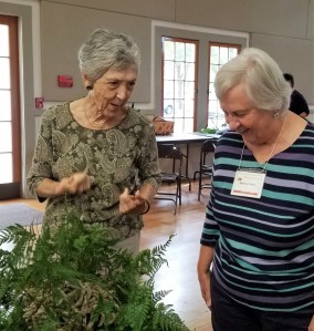 On the left Member Leah D. and Member Darlene L. discuss the use of ferns.